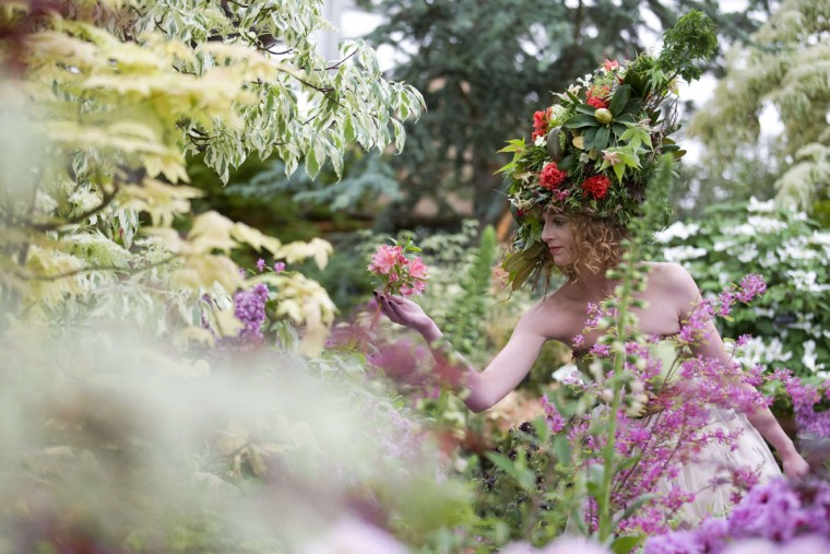 "A model dressed as a garden using fresh flowers and foliage from different continents poses for pictures on the Hillier ""Crossing Continents"" stand at the 2015 Chelsea Flower Show in London on May 18, 2015. The Chelsea flower show, held annually in the grounds of the Royal Hospital Chelsea, will run this year from May 19-23. (AFP Photo/Justin Tallis)"