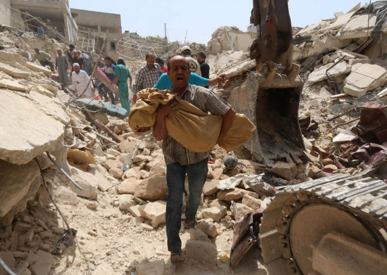 A Syrian man carries a body after it was removed from the rubble of buildings following a reported barrel bomb attack by government forces on the Qadi Askar district of the northern Syrian city of Aleppo on May 20, 2015. (Zein al-Rifai/Getty Images)
