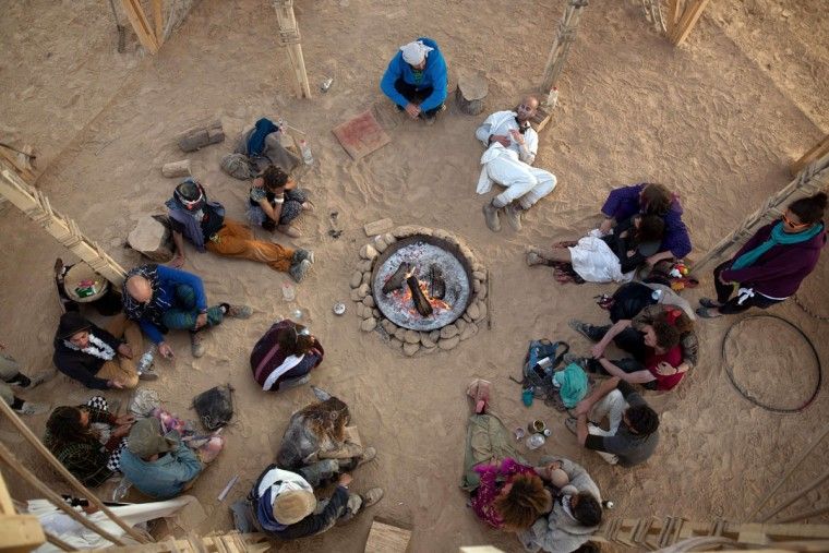 People sit around bonfire inside a Temple structure during the 2015 Midburn festival in the Negev Desert near the Israeli kibbutz of Sde Boker on May 22, 2015. (MENAHEM KAHANA/AFP/Getty Images)