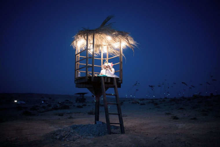 A couple dressed in costumes sit inside a hut during the 2015 Midburn festival in the Negev Desert near the Israeli kibbutz of Sde Boker on May 21, 2015. (MENAHEM KAHANA/AFP/Getty Images)