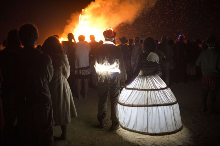 People in costumes watch as the wooden effigy burns during the 2015 Midburn festival in the Negev Desert near the Israeli kibbutz of Sde Boker on May 22, 2015. (MENAHEM KAHANA/AFP/Getty Images)