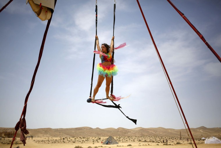 An Israeli woman swings in the air during the 2015 Midburn festival in the Negev Desert near the Israeli kibbutz of Sde Boker on May 23, 2015. (GALI TIBBON/AFP/Getty Images)