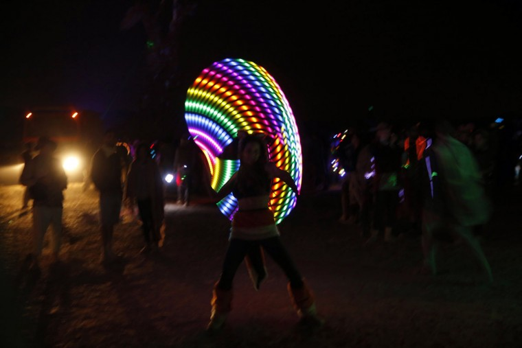 An Israeli girl dances with an illuminated hula hoop during the 2015 Midburn festival in the Negev Desert near the Israeli kibbutz of Sde Boker on May 22, 2015. (GALI TIBBON/AFP/Getty Images)