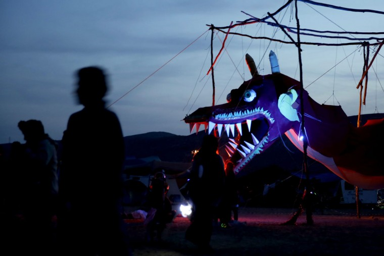 Israelis walk past a dragon installation during the 2015 Midburn festival in the Negev Desert near the Israeli kibbutz of Sde Boker on May 22, 2015. (GALI TIBBON/AFP/Getty Images)