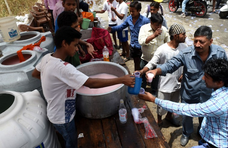Indian volunteers distribute free cold sweet water on a street in New Delhi, on May 28, 2015. More than 1,100 people have died in a blistering heatwave sweeping India, authorities said, as forecasters warned searing temperatures would continue. (Money Sharma/AFP/Getty Images)