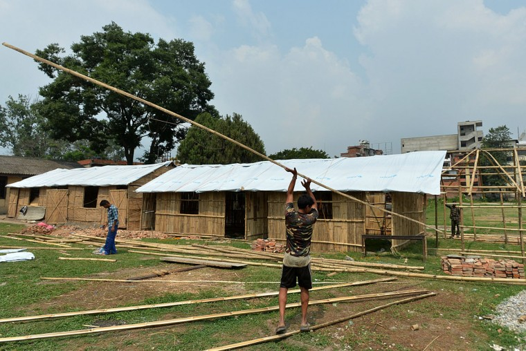 Nepalese workers carry bamboo poles as they build a temporary school building ahead of a planned reopening of schools in Kathmandu on May 30, 2015. More than 8,600 people died in two earthquakes that hit Nepal on April 25, 2015, and May 12, destroying nearly half a million houses and leaving thousands without food or water. (Ishara S. Kodikara/AFP/Getty Images)