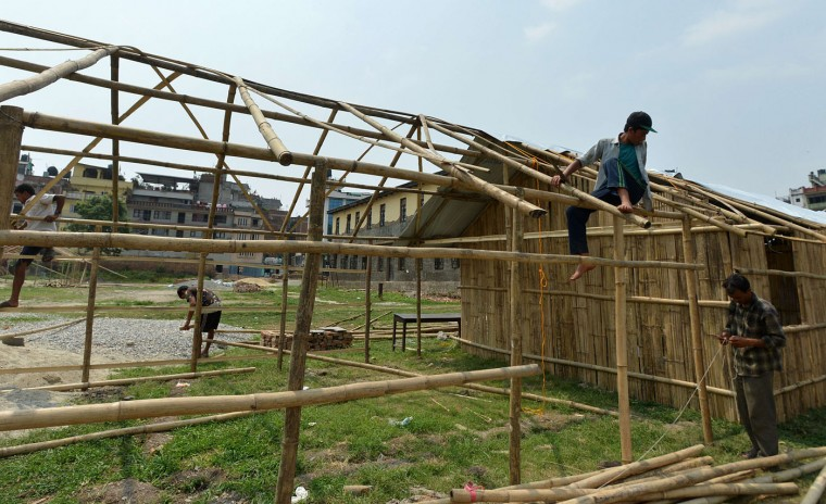 Nepalese workers build a temporary school building ahead of a planned reopening of schools in Kathmandu on May 30, 2015. More than 8,600 people died in two earthquakes that hit Nepal on April 25, 2015, and May 12, destroying nearly half a million houses and leaving thousands without food or water. (Ishara S. Kodikara/AFP/Getty Images)