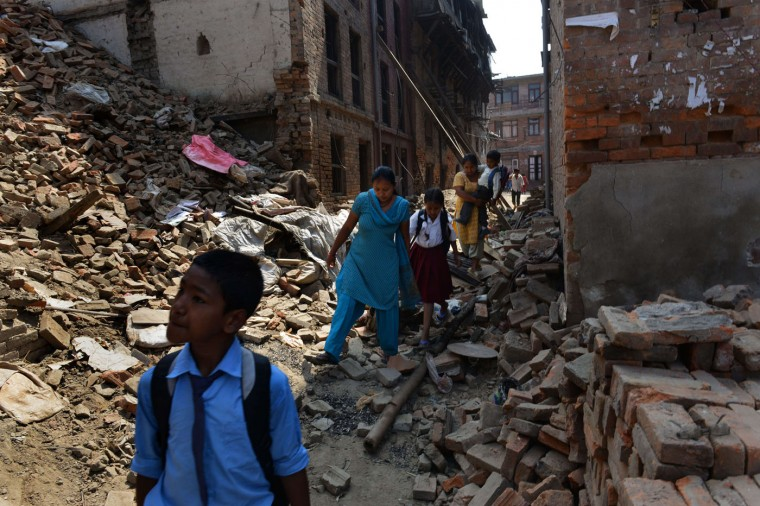 Nepalese parents walk with their children past damaged buildings to school in Bhaktapur on the outskirts of Kathmandu on May 31, 2015. Schools are reopening in Nepal following a devastating earthquake on April 25, 2015 which killed over 8,600 people, and damaged nearly 8,000 schools and 30,000 classrooms. (Prakash Mathema/AFP/Getty Images)