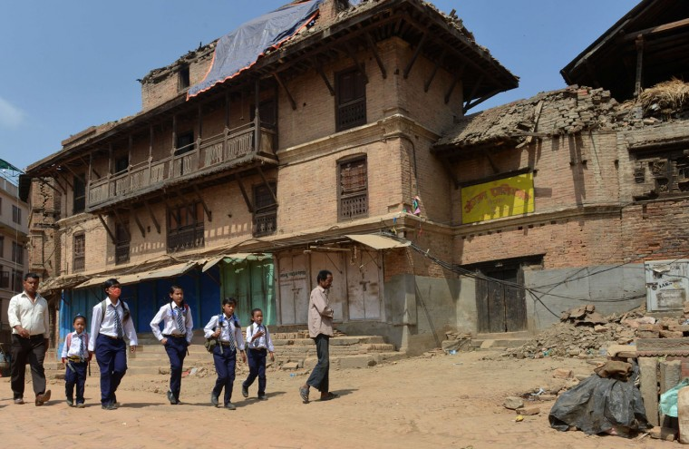 Nepalese students walk past damaged buildings to school in Bhaktapur on the outskirts of Kathmandu on May 31, 2015. Schools are reopening in Nepal following a devastating earthquake on April 25, 2015 which killed over 8,600 people, and damaged nearly 8,000 schools and 30,000 classrooms. (Prakash Mathema/AFP/Getty Images)