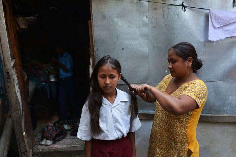Nepalese schoolgirl Ankita Kapali (L), 11, looks on as she has her hair done before leaving for school in Bhaktapur in Bhaktapur on the outskirts of Kathmandu on May 31, 2015. Schools are reopening in Nepal following a devastating earthquake on April 25, 2015 which killed over 8,600 people, and damaged nearly 8,000 schools and 30,000 classrooms. (Prakash Mathema/AFP/Getty Images)