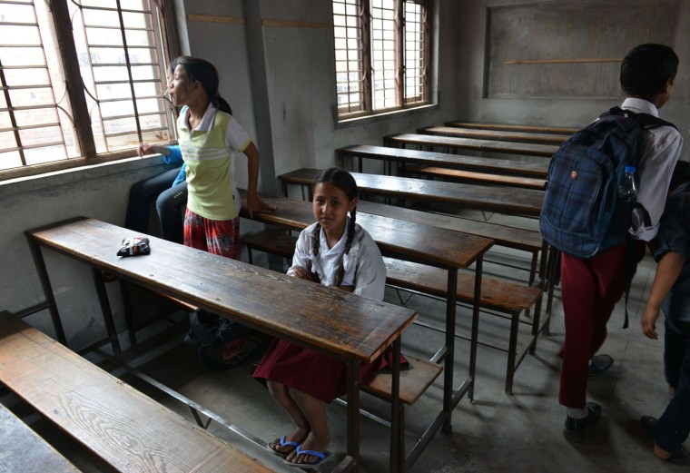 Nepalese schoolgirl Ankita Kapali, 11, looks on as she sits in a classroom at her school in Bhaktapur in Bhaktapur on the outskirts of Kathmandu on May 31, 2015. Schools are reopening in Nepal following a devastating earthquake on April 25, 2015 which killed over 8,600 people, and damaged nearly 8,000 schools and 30,000 classrooms. (Prakash Mathema/AFP/Getty Images)
