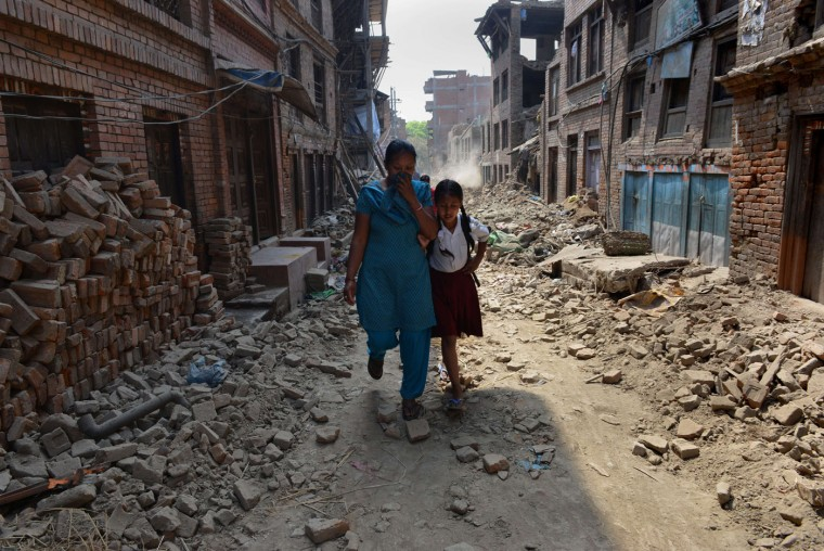 Nepalese schoolgirl Ankita Kapali (R), 11, walks with her mother past damaged buildings to school in Bhaktapur in Bhaktapur on the outskirts of Kathmandu on May 31, 2015. Schools are reopening in Nepal following a devastating earthquake on April 25, 2015 which killed over 8,600 people, and damaged nearly 8,000 schools and 30,000 classrooms. (Prakash Mathema/AFP/Getty Images)