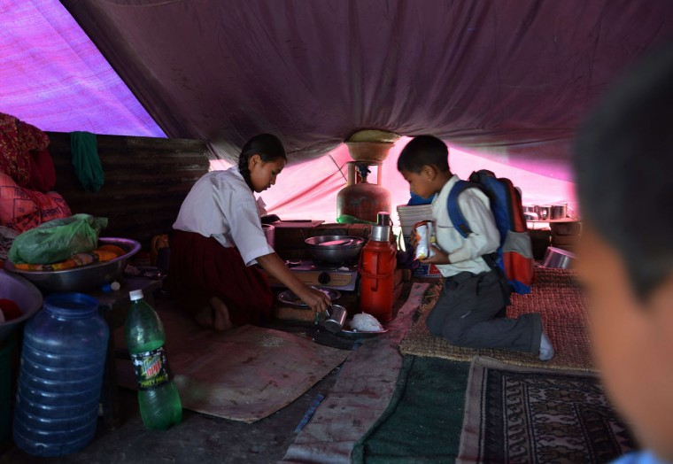 Nepalese schoolgirl Ankita Kapali (L), 11, prepares food before leaving for school in Bhaktapur in Bhaktapur on the outskirts of Kathmandu on May 31, 2015. Schools are reopening in Nepal following a devastating earthquake on April 25, 2015 which killed over 8,600 people, and damaged nearly 8,000 schools and 30,000 classrooms. (Prakash Mathema/AFP/Getty Images)