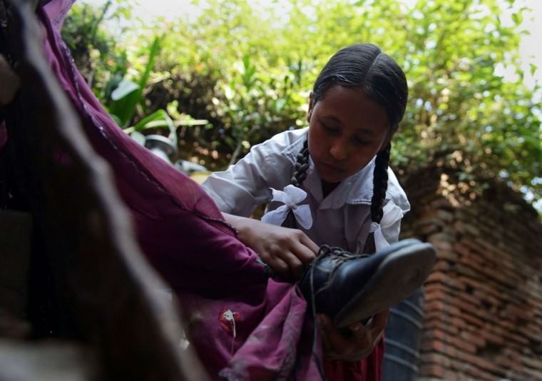 Nepalese schoolgirl Ankita Kapali, 11, cleans her shoes as she prepares to return to school in Bhaktapur in Bhaktapur on the outskirts of Kathmandu on May 31, 2015. Schools are reopening in Nepal following a devastating earthquake on April 25, 2015 which killed over 8,600 people, and damaged nearly 8,000 schools and 30,000 classrooms. (Prakash Mathema/AFP/Getty Images)