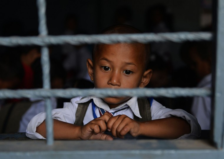Nepalese schoolboy Jaswoba Chheakna, 4, looks out of the window of a schoolroom in Bhaktapur on the outskirts of Kathmandu on May 31, 2015. Schools are reopening in Nepal following a devastating earthquake on April 25, 2015 which killed over 8,600 people, and damaged nearly 8,000 schools and 30,000 classrooms. (Prakash Mathema/AFP/Getty Images)