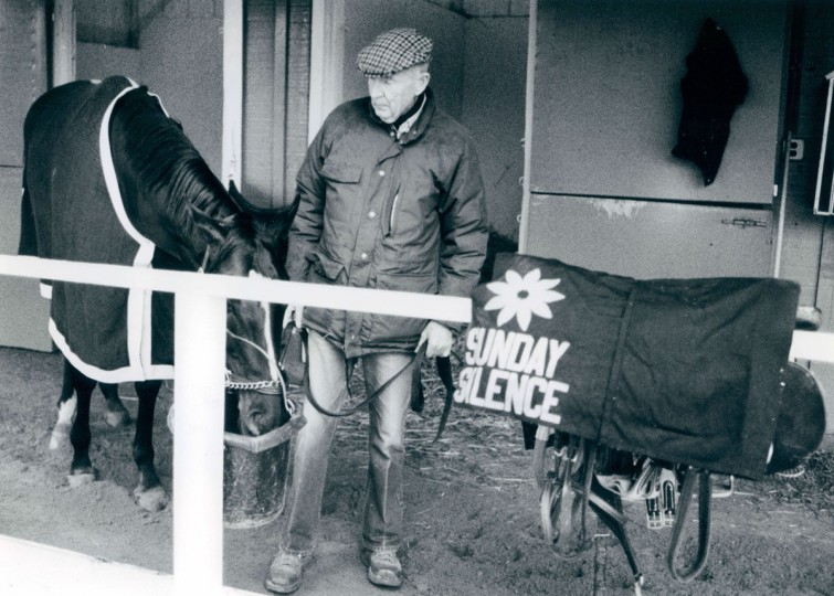Trainer Charlie Whittingham lets his Derby winning horse stop for a drink of water as the two walked around the Preakness Barn. (Bo Rader/Baltimore Sun, 1989)