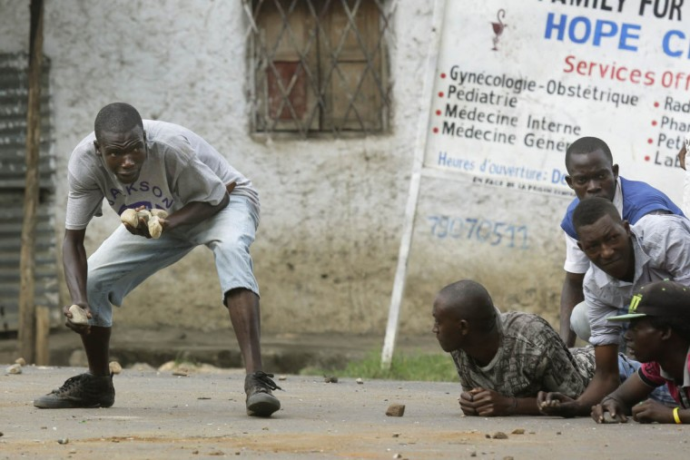 Demonstrators face off with police in the Musaga neighborhood of Bujumbura, Burundi, Wednesday May 20, 2015. Police returned to the neighborhood in full force Wednesday, firing live rounds and tear gas to disperse demonstrators protesting the president's decision to seek a third term. ( AP Photo/Jerome Delay)