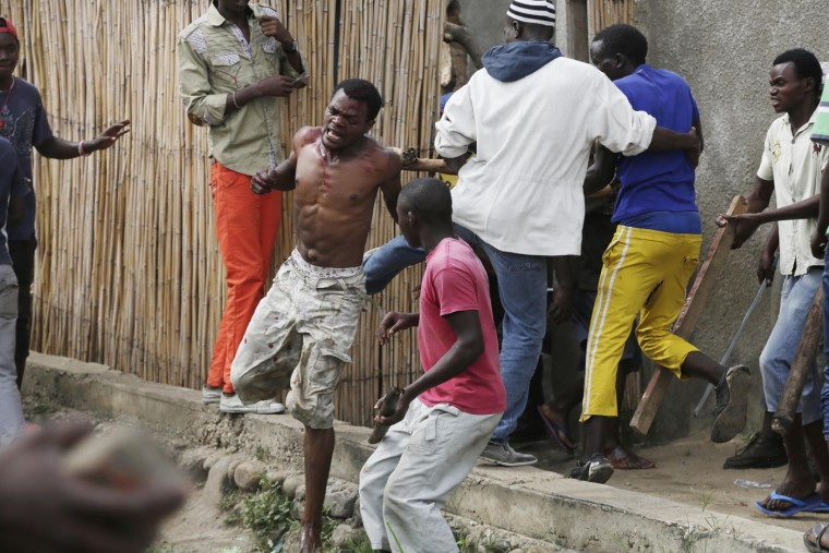 Jean Claude Niyonzima, a suspected member of the ruling party's Imbonerakure youth militia, flees from his house while surrounded by a mob of demonstrators protesting against President Pierre Nkurunziza's decision to seek a third term in office, in the Cibitoke district of Bujumbura, Burundi, Thursday May 7, 2015. At least one protestor has died in clashed with the widely feared Imbonerakure militias and police, sending scores to the streets seeking revenge. This suspect eventually managed to flee under a hail of stones into a covered sewer, where he remained till the army fired shots into the air to disperse the crowd. (AP Photo/Jerome Delay)