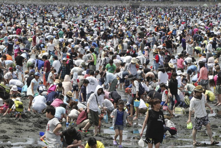 "Beachgoers dig for clams during the annual holidays known as ""Golden Week"", in Yokohama near Tokyo, Monday, May 4, 2015. (AP Photo/Koji Sasahara)"