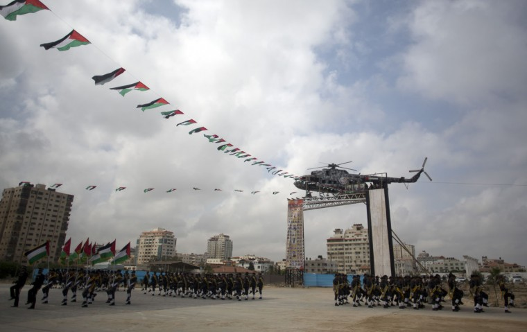 Palestinian Hamas security forces march next to the wreckage of late Palestinian President Yasser Arafat's helicopter, installed on a structure, during a police academy graduation ceremony in Gaza City, Thursday, May 21, 2015. (AP Photo/Khalil Hamra)