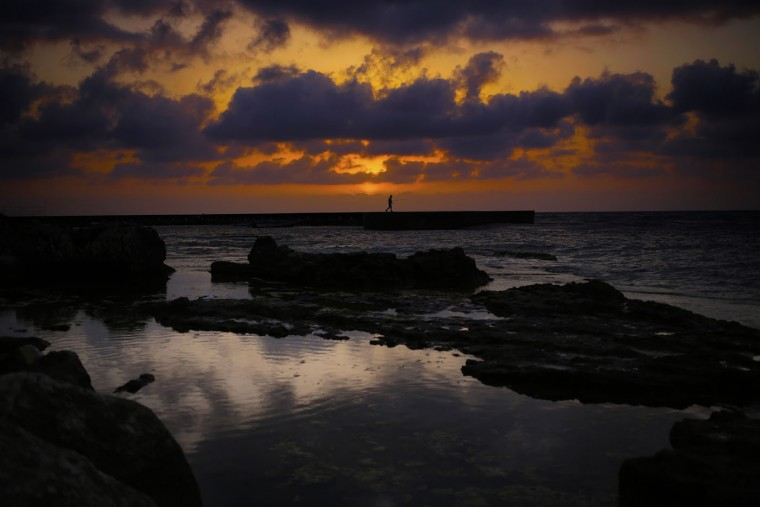 A man stands on a breakwater along the Beirut coastline as the sun sets over the Mediterranean Sea in Lebanon, Thursday, May 28, 2015. (AP Photo/Hassan Ammar)