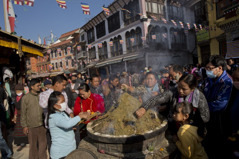 Nepalese Buddhists light incense sticks at the Boudhanath Stupa during Buddha Jayanti, or Buddha Purnima, festival in Kathmandu, Nepal, Monday, May 4, 2015. Hundreds of people have visited Buddhists shrines and monasteries in Nepalís quake-wracked Kathmandu on Buddha Purnima to pray for the country and the people who suffered during April 25 earthquake. The festival of Buddha Purnima marks the triple events of Gautam Buddha's life: his birth, his enlightenment and his attaining a state of Nirvana that frees believers from the circle of death and rebirth.(AP Photo/Bernat Amangue)