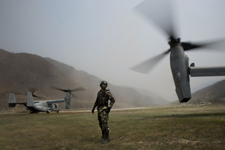 A Nepalese soldier stands between two U.S. Ospreys which are used to assist the deployment of Nepalese soldiers in the quake affected mountainous areas in Manthali, Nepal, Thursday, May 7, 2015. The April 25 earthquake killed thousands and injured many more as it flattened mountain villages and destroyed buildings and archaeological sites in Kathmandu.(AP Photo/Bernat Armangue)