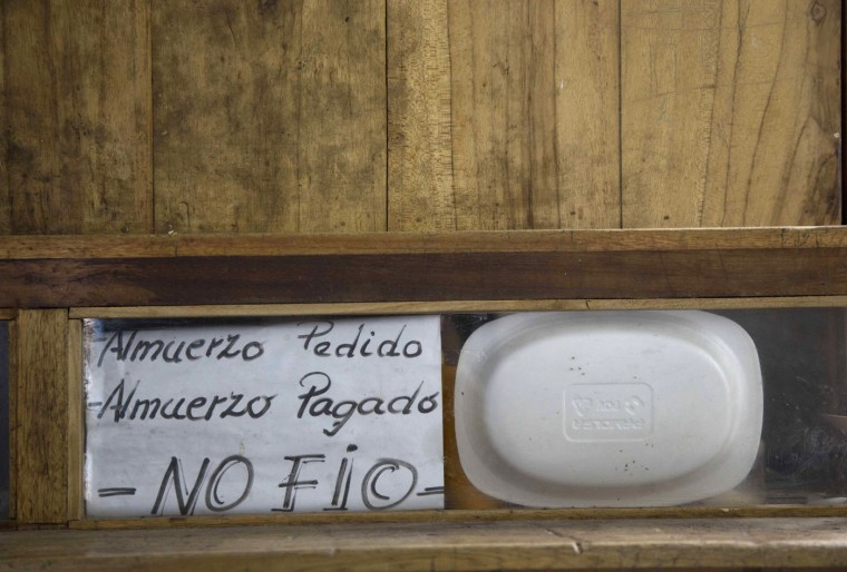 "In this April 14, 2015 photo, a handwritten sign that reads in Spanish ""Ordered lunch. Paid lunch. I don't trust"" is posted inside a prison cell at the now empty Garcia Moreno Prison, during a guided tour for the public in Quito, Ecuador. The prisoner who used this cell sold food and ran a small general store inside, selling items to his fellow inmates. (AP Photo/Dolores Ochoa)"