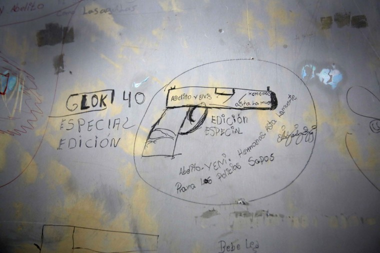 "This April 7, 2015 photo shows the wall of a jail cell covered with drawings and messages inside the now empty Garcia Moreno Prison, during a guided tour for the public in Quito, Ecuador. The Spanish language messages around the drawing encourage people to kill abusive police with a Glock special edition 40 gun. Part of it reads ""Brothers. Until death. For the abusive police."" (AP Photo/Dolores Ochoa)"