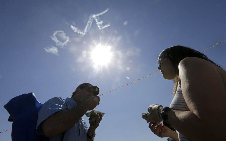 As a skywriter spells a message above, JJ Fisse, left, and his wife Laura Frisse, of New Orleans, eat a Cochon de Lait Po-Boy from Love At First Bite Catering at the New Orleans Jazz and Heritage Festival in New Orleans, Friday, May 1, 2015. Although the festival is mostly known for its diversity of musical acts big and small, festival-goers also rave about the food available, featuring Louisiana and Southern culinary offerings from over 70 vendors spread across the festival grounds. (AP Photo/Gerald Herbert)