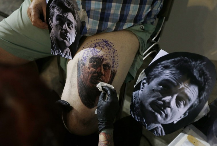 A tattoo artist creates a tattoo portrait of American actor Robert De Niro on a man's leg, during the annual Athens Tattoo Convention in Athens, Sunday, May 17, 2015. About 230 artists from Greece and abroad took part in the three-day event attracted thousands of visitors. (AP Photo/Thanassis Stavrakis)