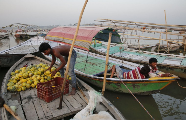 An Indian farmer unloads watermelons, a summer fruit, from his boat on the bank of the river Ganges, in Allahabad, India , Thursday, May 28, 2015. Eating onions, lying in the shade and splashing into rivers, Indians were doing whatever they could Thursday to stay cool during a brutal heat wave that has killed more than 1,000 in the past month. (AP Photo/Rajesh Kumar Singh)