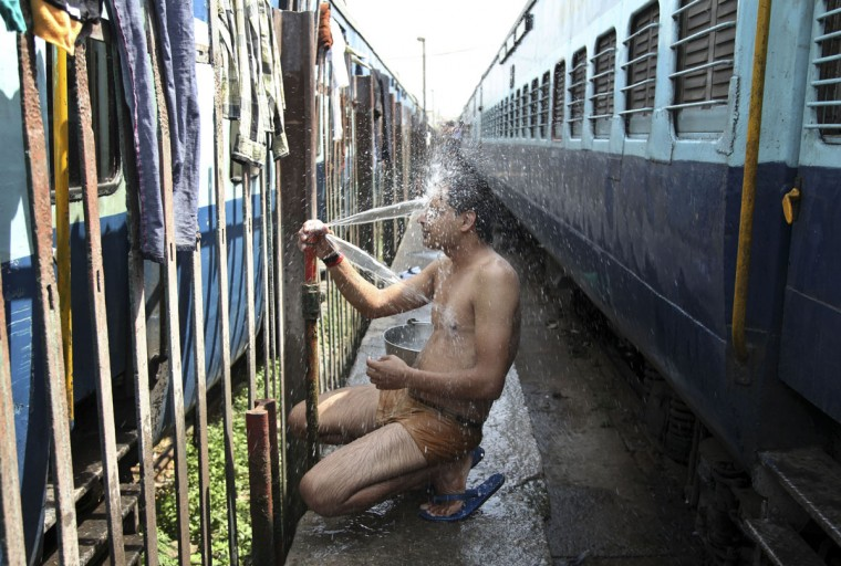 An Indian passenger takes a bath beside rail tracks on a hot summer day at a railway station in Jammu, India, Monday, May 25, 2015. Severe heat wave conditions continue to prevail at several places in northern India with temperatures reaching 48 degrees Celsius (118 degrees Fahrenheit). (AP Photo/Channi Anand)