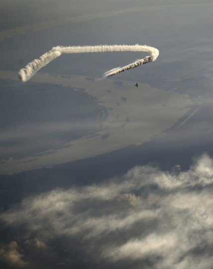 In this aerial photo, skywriter Nathan Hammond writes a message over the Mississippi River and New Orleans, Saturday, May 2, 2015. Hammond was commissioned by local entrepreneur Frank Scurlock to write positive, inspiring messages over the city during the New Orleans Jazz and Heritage Festival. (AP Photo/Gerald Herbert)