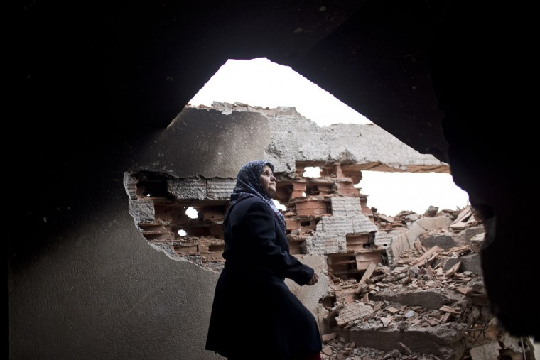 Habibe Biyali walks up a flight of stairs in her house heavily damaged by fighting in Kumanovo, Macedonia, Monday, May 11, 2015. Residents are returning to their homes in a northern Macedonian town where a fierce weekend battle between special police units and alleged ethnic Albanian militants left 22 dead and at least 37 injured. (AP Photo/Marko Drobnjakovic)
