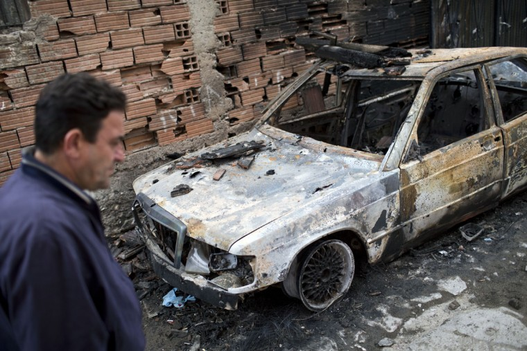 A man walks by a car destroyed in clashes in Kumanovo, Macedonia, Monday, May 11, 2015. Residents are returning to their homes in a northern Macedonian town where a fierce weekend battle between special police units and alleged ethnic Albanian militants left 22 dead and at least 37 injured. (AP Photo/Marko Drobnjakovic)