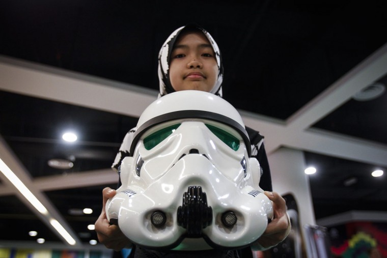 "A Malaysian Muslim girl poses with a Storm Trooper helmet at a Star Wars Day gathering in a mall downtown Kuala Lumpur, Malaysia, Saturday, May 2, 2015. Star Wars Day is observed by fans globally on May 4 with a slight change in the iconic catchphrase; from ""May the Force be with you"" to ""May the Fourth be with you"". (AP Photo/Joshua Paul)"