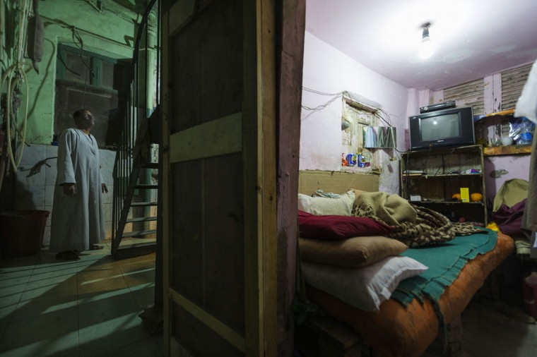 In this April 25, 2015 photo, Salama Osman waits for water to be boiled to make tea before going to bed in his room, where he lives under the emergency stairs in the back of an apartment building where he works, in Cairo, Egypt. Osman is a ìbawaab,î one of likely tens of thousands of migrant workers across Cairo who function as doormen, car parkers, errand runners, night watchmen, gardeners and just about anything. (AP Photo/Hiro Komae)