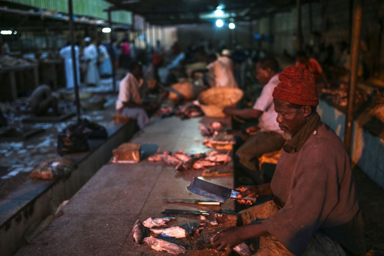 In this Thursday, April 16, 2015 photo, a Sudanese fisherman cleans fish before selling them at Omdurman fish market, which operates before dawn until sunrise, in Khartoum, Sudan. (AP Photo/Mosa'ab Elshamy)