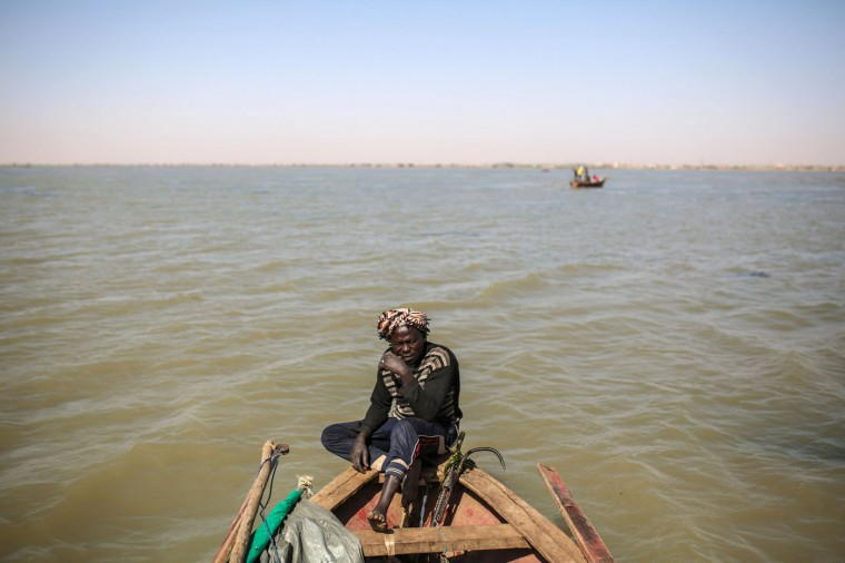 In this Wednesday, April 15, 2015 photo, Younis Hamad al-Nil, 35, sails his wooden boat on the Nile River on the outskirts of Khartoum, Sudan. For 20 years, he has made the same trip, using his expert eye to search for suitable patches of water. Once satisfied with the location, he drops his net; retrieving it a half hour later to survey his haul. (AP Photo/Mosa'ab Elshamy)