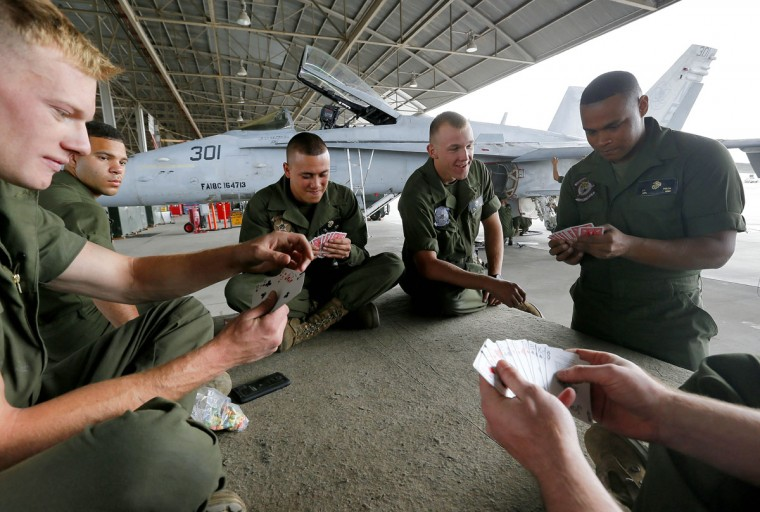 U.S. Marines play spades during a break at the 309th Aerospace Maintenance and Regeneration Group boneyard in Tucson, Ariz., on Thursday, May 21, 2015. The Marines are repairing F-A-18's to return to service at the 309th facility. (AP Photo/Matt York)