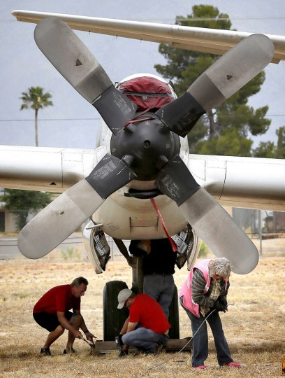 Crew members from the 309th Aerospace Maintenance and Regeneration Group boneyard secure a U.S. Navy Lockheed P-3C Orion anti-submarine aircraft at its storage site after its arrival at Davis-Monthan Air Force Base in Tucson, Ariz. on Friday, May 15, 2015. (AP Photo/Matt York)