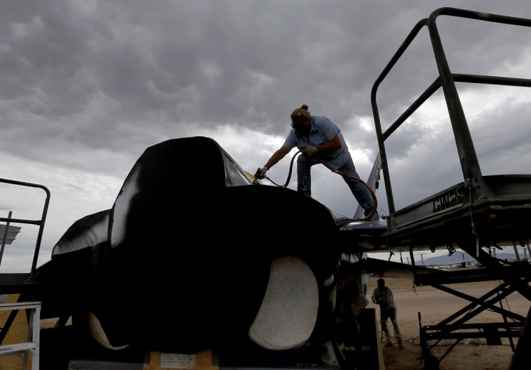 Preservation servicer Katy Shank sprays a sealing paint on a former NAVY Blue Angel F-18 at the 309th Aerospace Maintenance and Regeneration Group boneyard, Thursday, May 21, 2015, in Tucson, Ariz. The 309th is the United States Air Forceís aircraft and missile storage and maintenance facility and provides long and short-term aircraft storage, parts reclamation and disposal. (AP Photo/Matt York)