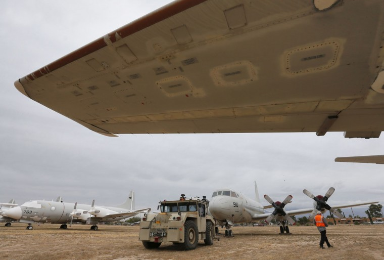 Crew members from the 309th Aerospace Maintenance and Regeneration Group boneyard tow a U.S. Navy Lockheed P-3 Orion into position on it's storage site after it's arrival, Friday, May 15, 2015 at Davis-Monthan Air Force Base in Tucson, Ariz. (AP Photo/Matt York)