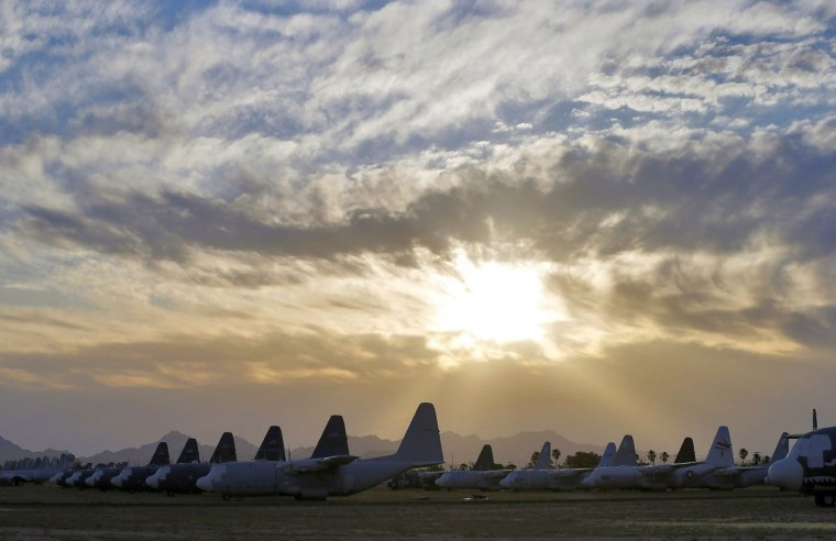 In this photo taken on Thursday, May 14, 2015, the sun sets over C-130 cargo planes at the 309th Aerospace Maintenance and Regeneration Group boneyard at Davis-Monthan Air Force Base in Tucson, Ariz. The 309th is the United States Air Force's aircraft and missile storage and maintenance facility and provides long and short-term aircraft storage, parts reclamation and disposal. (AP Photo/Matt York)