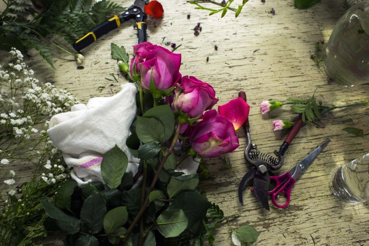 Roses wait to be arranged on a design table in a warehouse on Mother's Day, Sunday, May 10, 2015, at Vogt's Flowers in Flint, Mich. (Brittany Greeson/The Flint Journal-MLive.com via AP)