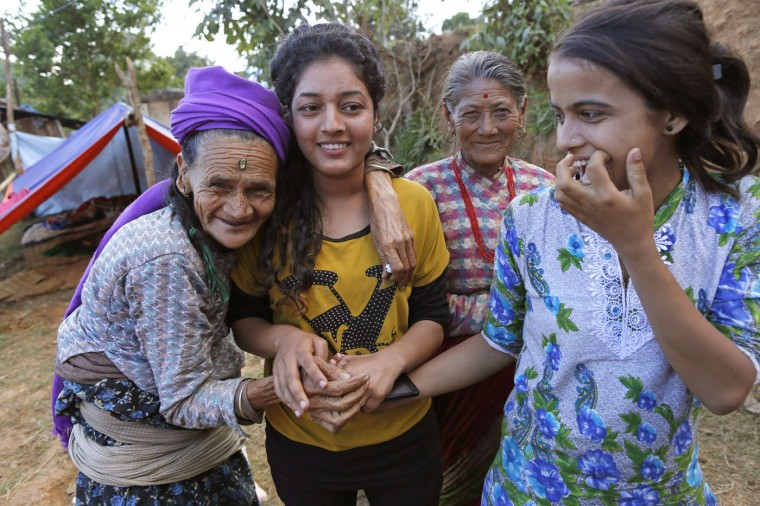 In this photo taken on Saturday, May 2, 2015, Loysyanri Khanal, 78, left, shares a moment with the young girls in their destroyed village of Pokharidanda, near the epicenter of the April 25 massive earthquake, in the Gorkha District of Nepal. (AP Photo/Wally Santana)