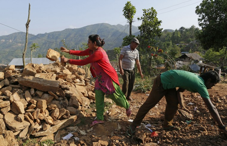 In this photo taken on Saturday, May 2, 2015, Santoshi Shrestha, 23, left, piles reusable rocks with neighbors in hopes to rebuild their home in the destroyed village of Pokharidanda, near the epicenter of last week's massive earthquake, in the Gorkha District of Nepal. (AP Photo/Wally Santana)