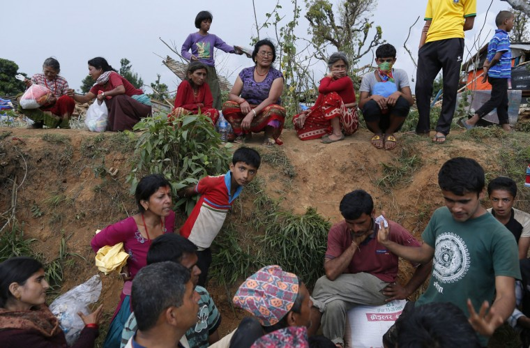 In this photo taken on Saturday, May 2, 2015, villagers gather to receive aid in the destroyed village of Pokharidanda, near the epicenter of the April 25 massive earthquake, in the Gorkha District of Nepal. (AP Photo/Wally Santana)