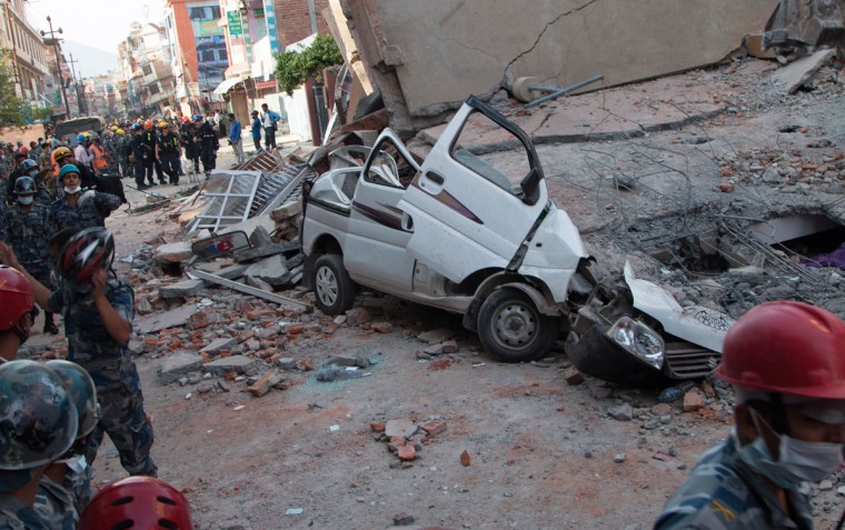 A car is seen smashed under the weight of a building that collapsed in an earthquake in Kathmandu, Nepal, Tuesday, May 12, 2015. A major earthquake has hit Nepal near the Chinese border between the capital of Kathmandu and Mount Everest less than three weeks after the country was devastated by a quake. (AP Photo/Ranup Shrestha)